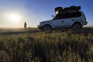 Woman standing by off-road vehicle at Makgadikgadi Pans, Botswana - VEGF00450