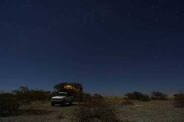 Tent on off-road vehicle on field against sky at night, Makgadikgadi Pans, Botswana - VEGF00453