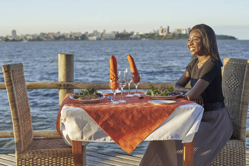 Young woman enjoying a dinner at the waterfront, Maputo, Mozambique - VEGF00459