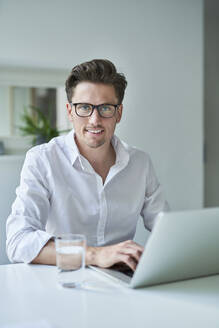 Portrait of smiling businessman using laptop in office - PNEF01784