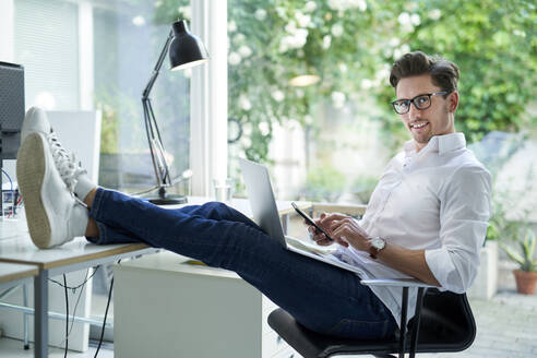 Portrait of smiling businessman using laptop and smartphone in office - PNEF01790