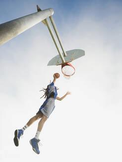 Black basketball player dunking ball in hoop - BLEF13796