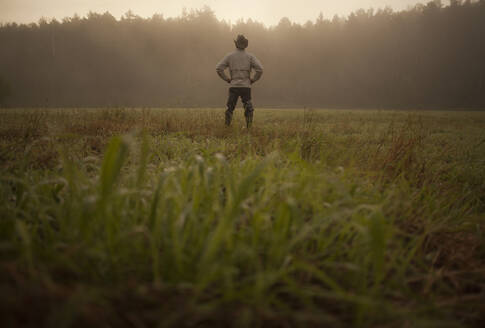 Mixed race man standing in field in rural landscape - BLEF13814