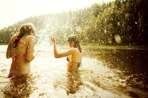Girls splashing together in lake - BLEF13817