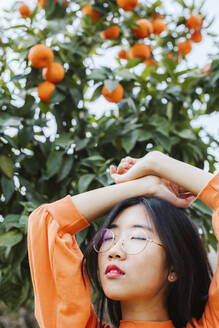 Portrait of young asian woman, tangerine tree in the background - LJF00610