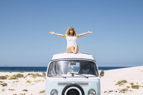 Woman sitting on the roof of a van, Fuerteventura - SIPF02062