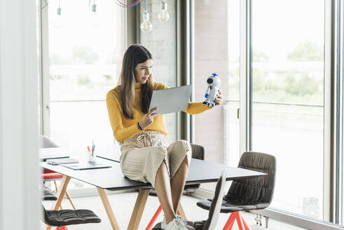 Young businesswoman sitting on table in office holding robot and tablet - UUF18476