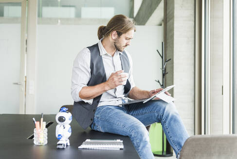 Young businessman sitting on table in office with tablet and cup of coffee - UUF18482