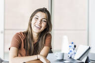 Portrait of laughing young businesswoman sitting at desk in office - UUF18515