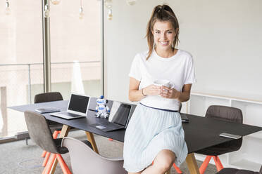 Portrait of smiling young businesswoman having coffee break in office - UUF18521
