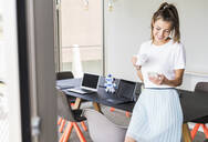 Smiling young businesswoman having coffee break in office looking at cell phone - UUF18524