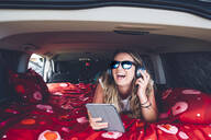 Pretty blonde woman with sunglasses and headphones in camping inside a van using tablet - OCMF00564