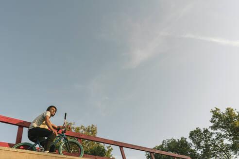 Young man with BMX bike at skatepark having a break - AHSF00739