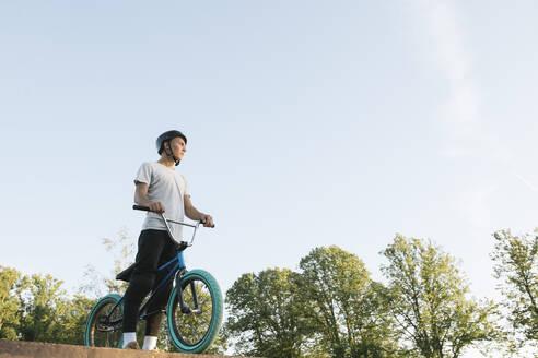 Young man with BMX bike at skatepark having a break - AHSF00742