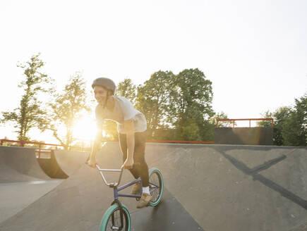 Happy young man riding BMX bike at skatepark at sunset - AHSF00745