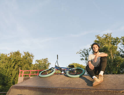 Young man with BMX bike at skatepark having a break - AHSF00757