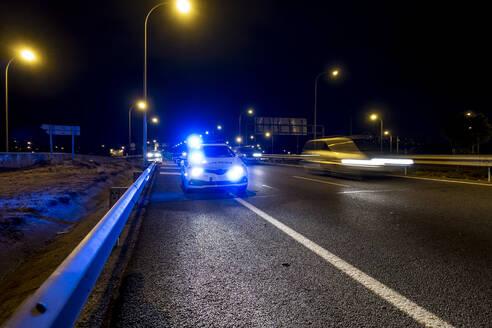Illuminated police car on road of Madrid during night - OCMF00568