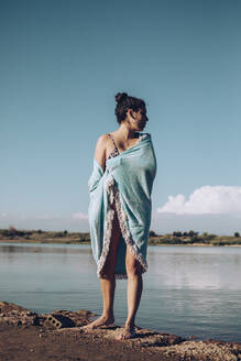 Young woman wrapped in a towel standing at lakeshore - ACPF00579