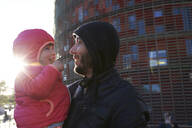 Happy father holding his daughter in the city at sunset in winter, Barcelona, Spain - GEMF03109