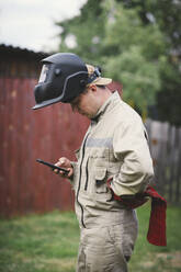 Man with welding mas, standing in backyard, using smartphone - EYAF00355