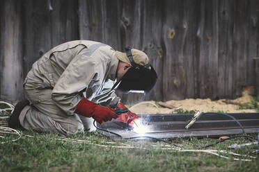 Man welding metal in his backyard - EYAF00358