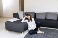 Portrait of relaxed woman with book in living room - FMKF05833