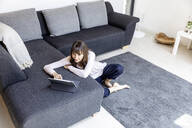 Relaxed woman using tablet in living room at home - FMKF05836
