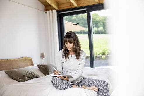 Woman using tablet on bed at home - FMKF05842