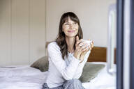 Relaxed woman with cup of coffee sitting on bed at home - FMKF05848
