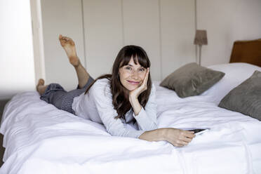 Portrait of relaxed woman lying on bed at home with tablet - FMKF05851