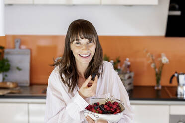 Portrait of happy woman wearing pyjama eating fruit in kitchen at home - FMKF05857