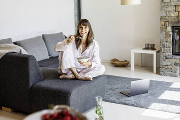 Portrait of smiling woman having breakfast on couch at home - FMKF05863