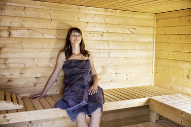 Woman relaxing in a sauna - FMKF05866