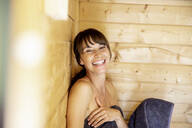 Portrait of happy woman in a sauna - FMKF05869