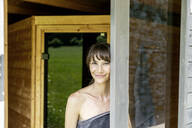 Portrait of smiling woman behind windowpane in a sauna - FMKF05872
