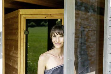 Portrait of smiling woman behind windowpane in a sauna - FMKF05872