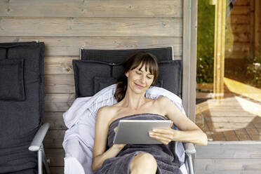 Woman relaxing on a lounge outside sauna using tablet - FMKF05875