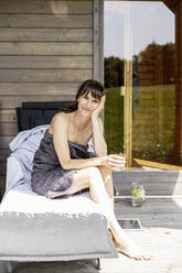 Portrait of woman relaxing on a lounge holding glass of water - FMKF05878