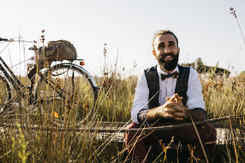 Well dressed man sitting on a wooden walkway in the countryside next to a bike - JRFF03589
