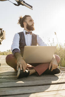 Well dressed man sitting on a wooden walkway in the countryside with laptop looking sideways - JRFF03598