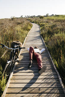 Well dressed man with laptop lying on a wooden walkway in the countryside next to a bike - JRFF03604