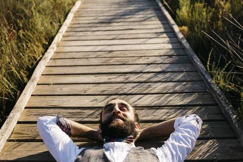 Well dressed man lying on a wooden walkway in the countryside - JRFF03607