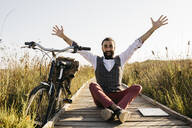Happy well dressed man sitting on a wooden walkway in the countryside next to a bike - JRFF03610