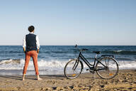 Well dressed man with his bike standing on a beach - JRFF03622