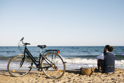 Well dressed man with his bike sitting on a beach - JRFF03628
