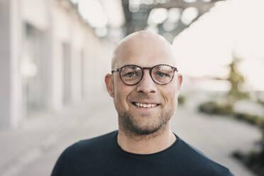 Portrait of smiling bald man wearing glasses - KNSF06205