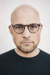 Portrait of serious bald man with beard wearing glasses - KNSF06208