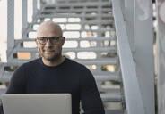 Portrait of bald man sitting on stairs using laptop - KNSF06211