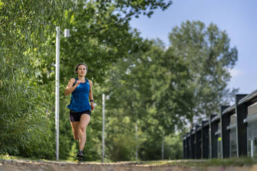 Young woman jogging on a woodchip trail - STSF02181