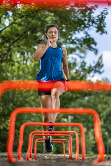 Young woman jumping over hurdles on a woodchip trail - STSF02184